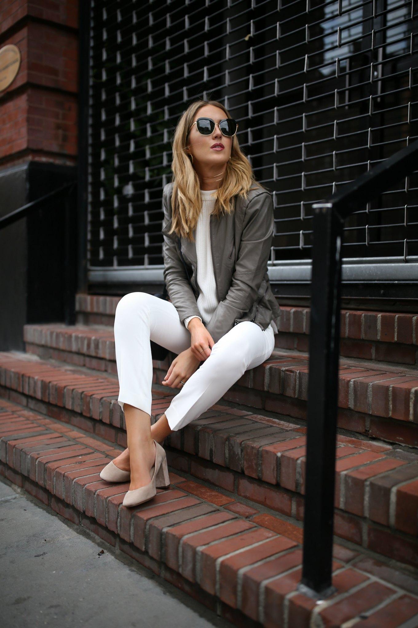 NYC时尚博主穿着灰色皮革机车夹克,白色针织上衣,白色锥形连衣裙,裤子绒面革裸色块状高跟鞋和超大太阳镜