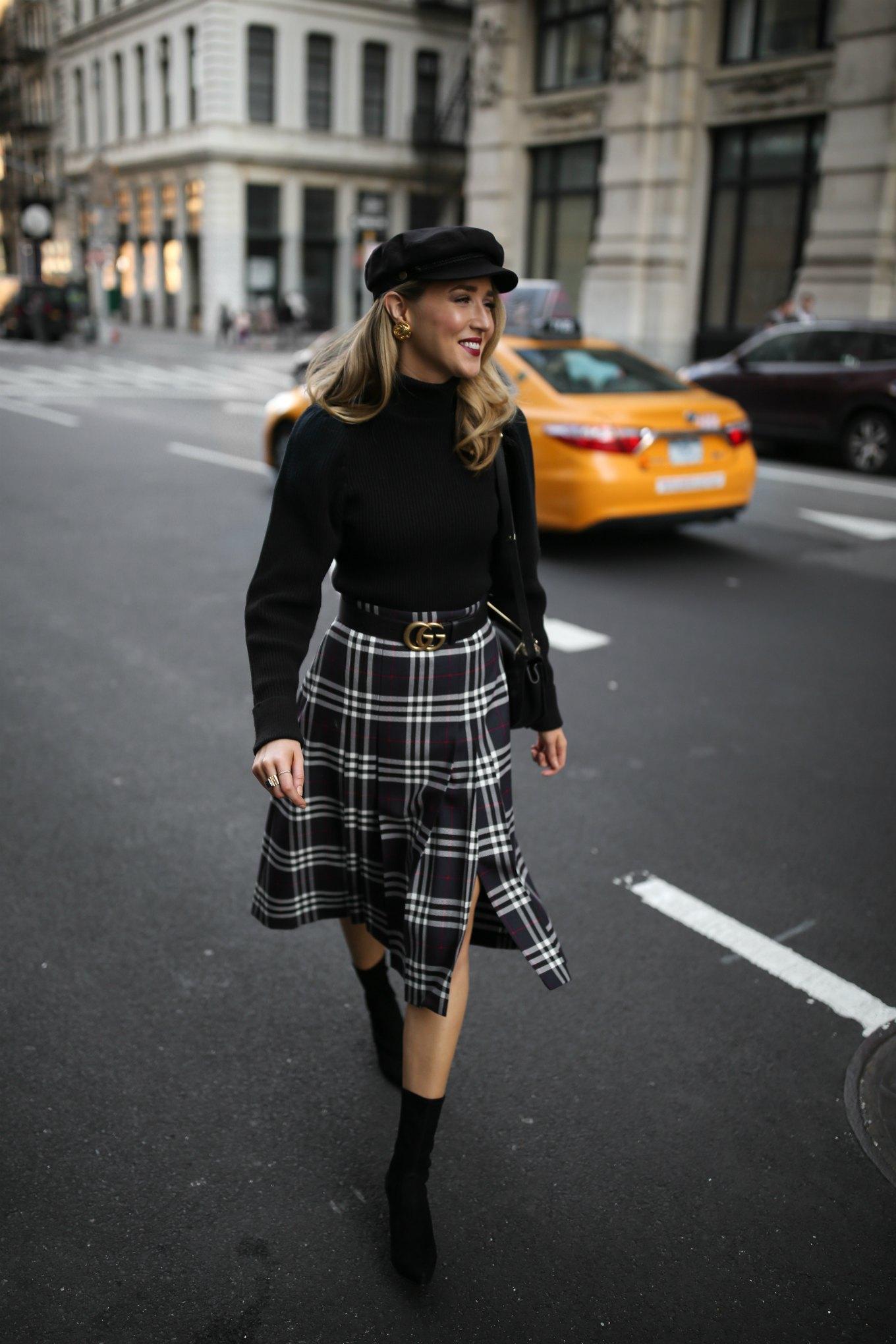 Mary Orton wears a Burberry plaid checked midi skirt, a black puffed-shoulder turtleneck, black Stuart Weitzman sock boots and a black baker boy cap