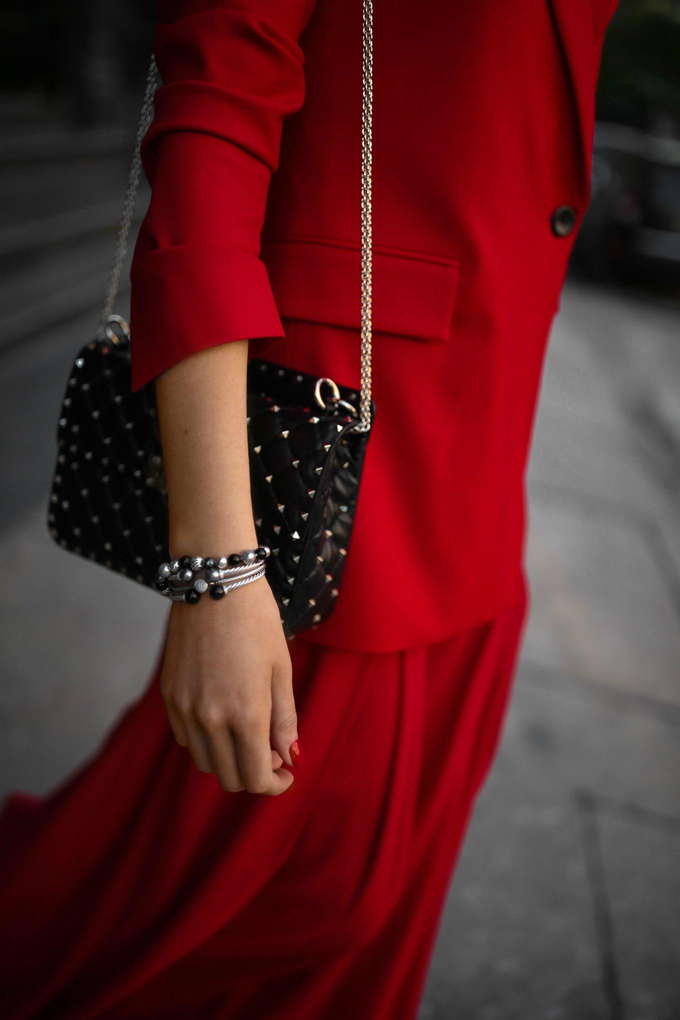 Mary Orton of Memorandum wears a Sara Battaglia red longline blazer, wide-leg pleated red trousers, a black Valentino studded leather shoulder bag and stacked David Yurman Solari bracelets