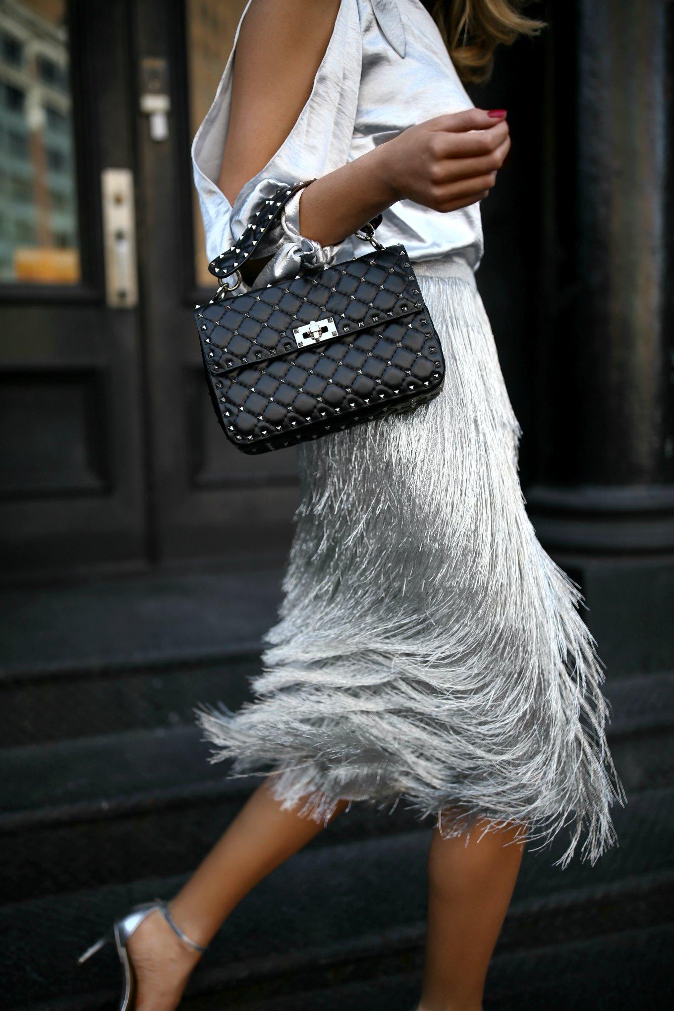 New York fashion blogger Mary Orton of Memorandum wears one shoulder metallic blouse by Rebecca Minkoff, Rachel Zoe metallic fringed silver midi skirt and Valentino studded leather shoulder bag