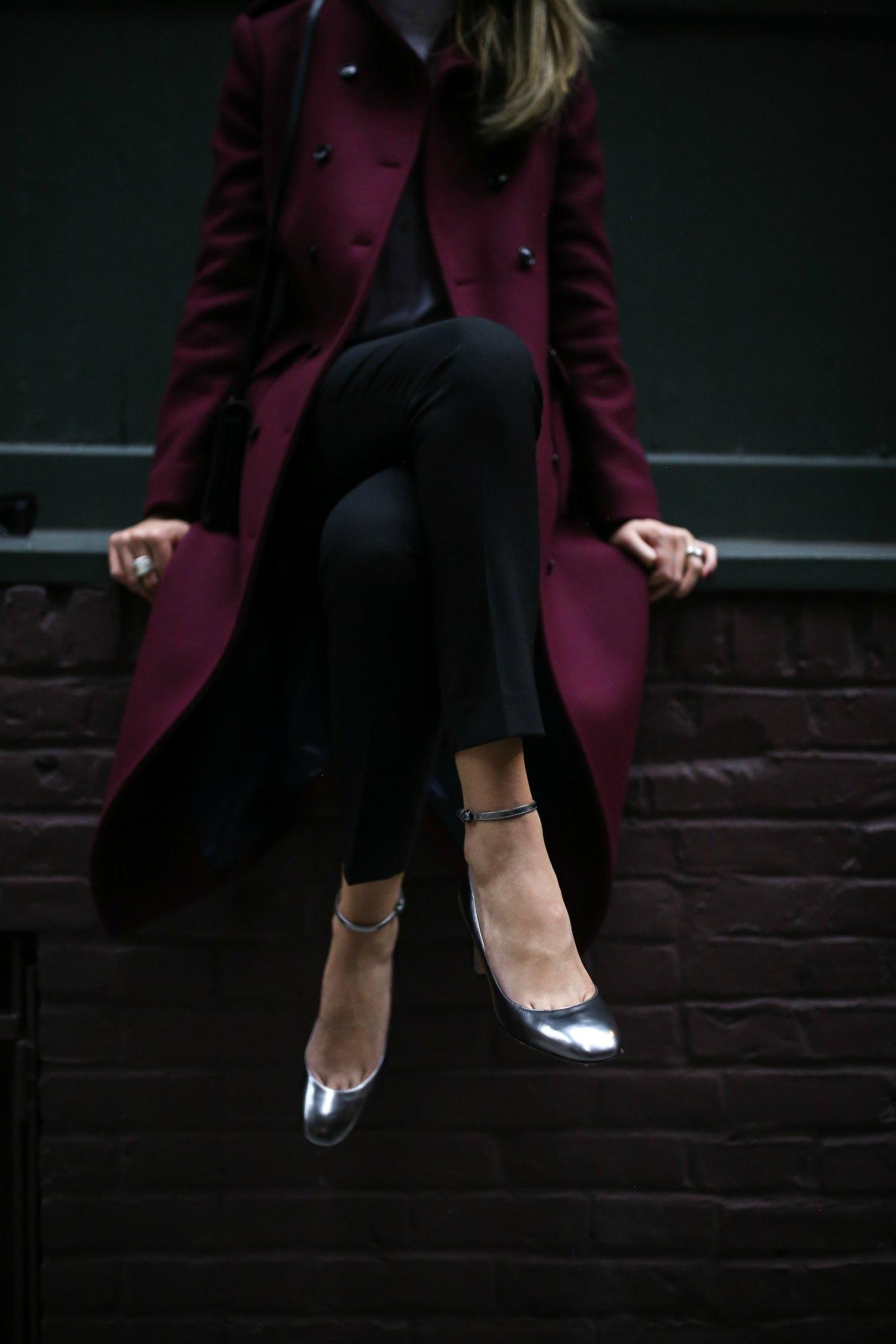 Mary Orton of Memorandum blog wears black tailored pants, long burgundy coat, white ruffle blouse, metallic block heel mary jane pumps and a black saint laurent bag